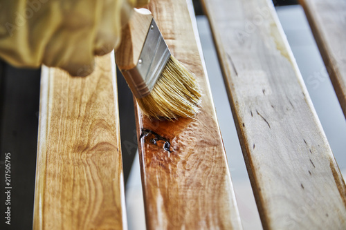 Paint Brush in a can of varnish in preparation to stain the wood slats - 217505795