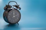 Black vintage alarm clock on blue background.