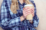Close-up view of young girl warms hands on a Cup of tea or coffee in a cold apartment sitting on the couch. Problem of high cost of heating concept.