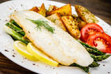 Fish dish - fried fish fillet with fried potatoes and vegetables - 217518112