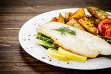 Fish dish - fried fish fillet with fried potatoes and vegetables - 217518137