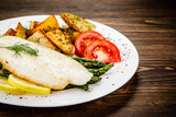 Fish dish - fried fish fillet with fried potatoes and vegetables - 217518159