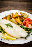 Fish dish - fried fish fillet with fried potatoes and vegetables - 217518194