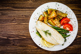 Fish dish - fried fish fillet with fried potatoes and vegetables - 217518327