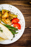 Fish dish - fried fish fillet with fried potatoes and vegetables - 217518366