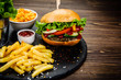 Leinwanddruck Bild - Tasty burger with chips served on stone plate