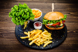 Tasty burger with chips served on stone plate  - 217518934
