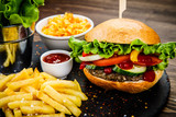 Tasty burger with chips served on stone plate  - 217518993