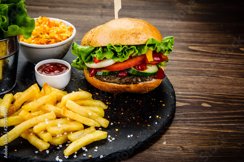 Tasty burger with chips served on stone plate  - 217518950