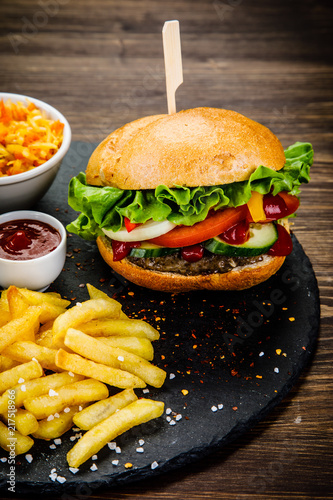 Tasty burger with chips served on stone plate  - 217518966