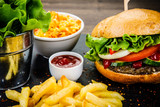 Tasty burger with chips served on stone plate  - 217519136
