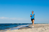 Young woman running on beach  - 217520134