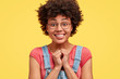 Photo of pretty happy dark skinned female with pleasant smile, keeps hands together, recieves good words of praise, has curly hair, poses against yellow background. Glad African American woman