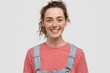 Smiling young freckled European female with positive expression, has cheerful look, dressed in red striped sweater with denim overalls, being in good mood, isolated over white studio background
