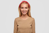 Young lovely blonde female has shinig smile, long hair, wears headband and beige casual sweater, expresses positive emotions, poses in studio, ready for date with boyfriend or meeting with friend - 217520769