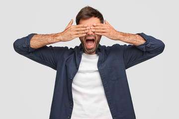 Handsome male covers eyes with both hands, keeps mouth widely, has stubble, dressed in shirt, waits for surprisement, isolated over white background. Young bearded man peecks through fingers. © Wayhome Studio