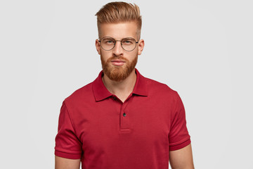 Candid shot of self confident serious Caucasian male with foxy hair and beard, dressed casually, looks directly at camera with mysterious expression, wears spectacles, isolated over white background © Wayhome Studio