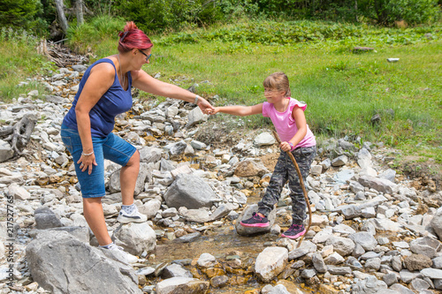 Mum helps her daughter to cross a mountain stream