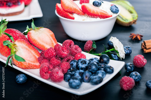 Berries of strawberries, blueberries and raspberries on a white saucer, proper nutrition, cottage cheese with berries
