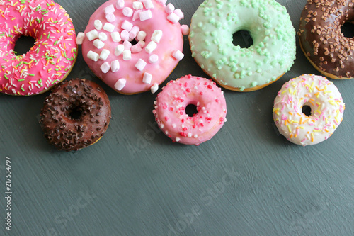 Photos of different donuts. Assorted colorful donuts in glaze close-up.