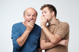Young caucasian son telling secret to his senior father. Senior man in shock opening his mouth. - 217535340