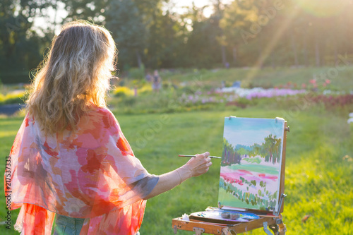 The painter paints oil paintings in the garden at sunset © allai