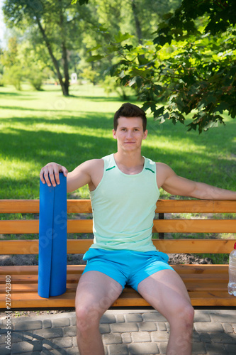 Wall mural Relax concept. Athlete relax on bench in park. Sportsman relax after yoga training. Relax and enjoy life