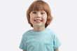 Leinwanddruck Bild - pretty red-haired kid showing his white teeth to the camera. little healthu boy wearing blue T-shirt