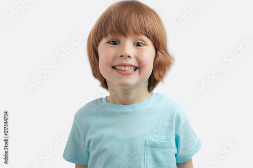 Leinwanddruck Bild pretty red-haired kid showing his white teeth to the camera. little healthu boy wearing blue T-shirt
