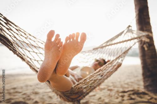 Leinwanddruck Bild Happy woman relaxing in hammock