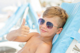 the boy on a sunny beach lies on a sun lounger in sunglasses and showing thumbs up - 217546985