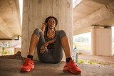 Young african american woman in sportswear is sitting on floor and enjoy listening her favorite music