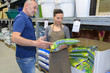 saleswoman recommending man a fertilizer for orchid plant in nursery