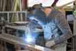 Leinwanddruck Bild - man welds at the factory