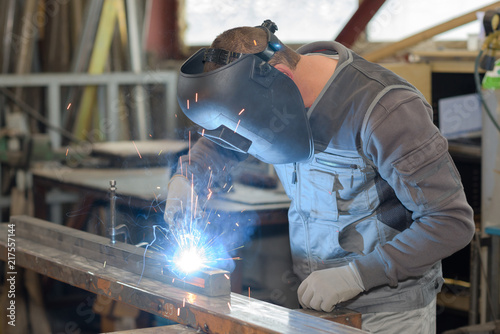 Leinwanddruck Bild man welds at the factory