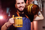 young attractive bearded brewer with a wooden mug in his hands and with a barrel of beer smiling at the background of the brewery - 217558373