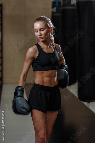blond girl in black boxing gloves posing in gym