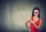 Elegant modern woman in dress pointing away - 217559388
