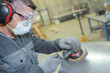 Leinwandbild Motiv man holding sanding metalic surface