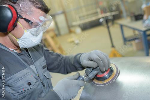 man holding sanding metalic surface - 217562554