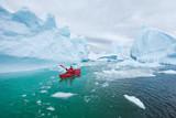 man paddling on kayak between ice in Antractica in Iceberg Graveyard, extreme winter kayaking, polar adventure near Pleneau island - 217568733