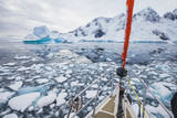 sailing boat in Antarctica, yacht navigation through icebergs and sea ice - 217568763