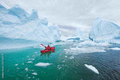 man paddling on kayak between ice in Antractica in Iceberg Graveyard, extreme winter kayaking, polar adventure near Pleneau island
