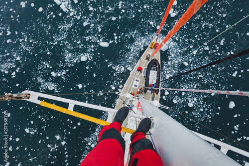 Canvas Zeilen sailing boat in Antarctica, extreme dangerous travel selfie, person feet standing on mast of a yacht with floating ice, top view, adventure