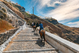 Tourists on donkeys climb the stairs from the port to the city Fira, modern capital of the Greek Aegean island,Santorini, Greece - 217576349