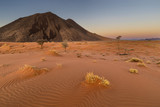 Red sand dune and black rock mountain - 217578595