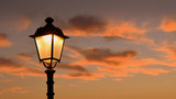 Orange leuchtender Abendhimmel, umrahmt von Zweigen unte antiker Laterne im Hintergrund  - 217582733