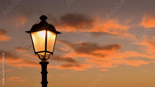 canvas print picture Orange leuchtender Abendhimmel, umrahmt von Zweigen unte antiker Laterne im Hintergrund