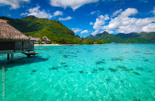 Foto Murales Tropical island resort with bungalow above the water on the amazing turquoise lagoon in Moorea.