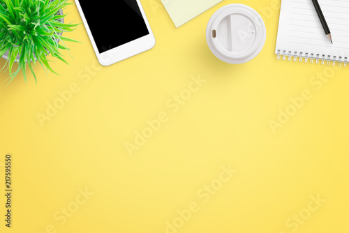 Foto Murales Yellow office desk composition with mobile phone, plant, coffee, notepad and pen. Flat lay.